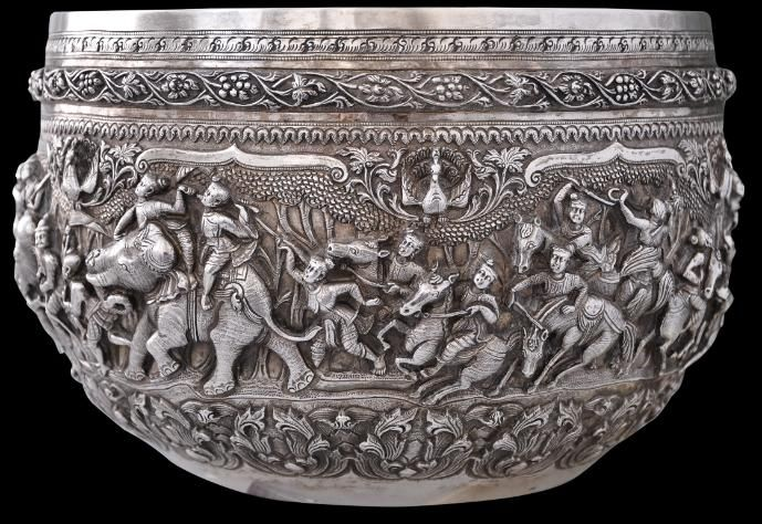 Superb Repoussed Silver Bowl Burma, circa 1870    This is a superb Burmese silver thabeik bowl.   The repousse work shows two short scenes and one very long one. On small scene appears to show a princess or queen being beckoned to leave her sitting  platform or throne. The next shows here in a traditional bullock driven wooden cart. The remainder of the bowl - almost all the way around - is taken up by a single, epic battle scene.