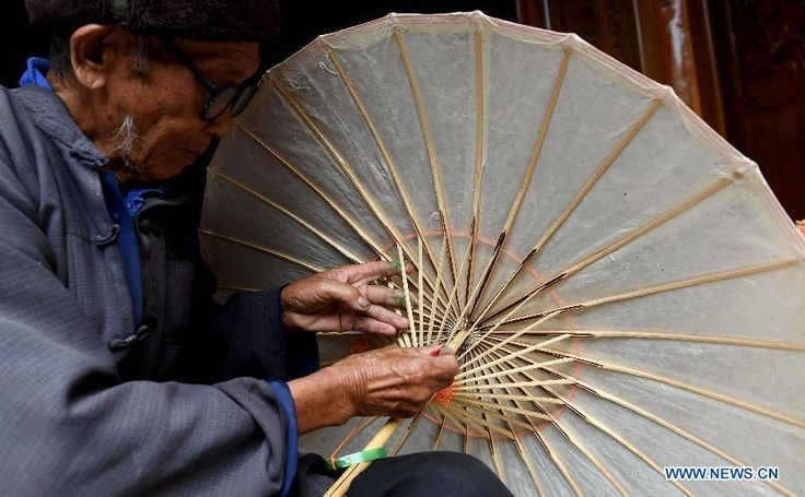 Craftsman and inheritor Zheng Yinghai, 89, makes oil-paper umbrellas in Yunyang village of Tengchong, Yunnan Province, July 22, 2015.  Made of oiled paper and bamboo frame, oil-paper umbrella is a traditional Chinese handicraft.  http://www.chinatraveltourismnews.com/2015/07/delicate-oil-paper-umbrellas.html
