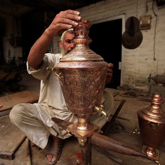A craftsman puts final touches to a decoration piece of tea kettle, at a workshop in Peshawar.  PHOTO: AFP  #crafts #pottery #copper #photography #potd #photooftheday #instadaily #instagood #igers #peshawar #punjab #karachi #islamabad #lahore #pakistan #instatravel #instapakistan