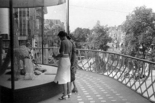 Tweede Wereldoorlog. Utrecht. Twee dames bekijken de etalages op een van de balkons van het nieuwe gebouw van de Galeries Modernes in 1941. Op de achtergrond een overzicht van de Oude Gracht met brug.
