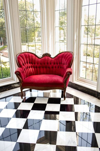 I adore this scarlet tufted love seat juxtaposed with the checkered floor
