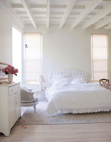 Photographer Amy Neunsinger transformed her Los Angeles house into a simple yet modern home. In the master bedroom, the pickled white wood floors combined with white walls create an ethereal feeling. The headboard and bedding are from Shabby Chic.