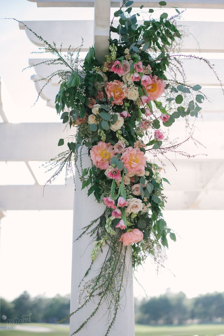 cascading from the top of the wedding gazebo column is a grand floral arrangement of coral charm peonies, tuberose, quicksand rose, cappuccino rose, peach stock, pink fringe tulip, pink begonia blossoms, white spirea branches, porcelina spray rose, vendela rose, italian variegated pittosporum, silver dollar eucalyptus, vines and greenery.