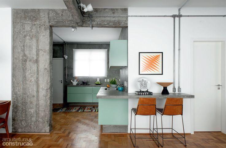 Na cor verde menta (ref. 83), os armários da cozinha (Securit) se destacam sobre o revestimento de cimento queimado no projeto de reforma do apartamento pequeno, por Paulo Mencarini.