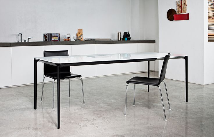Slim table with black Glove chairs in a modern kitchen.