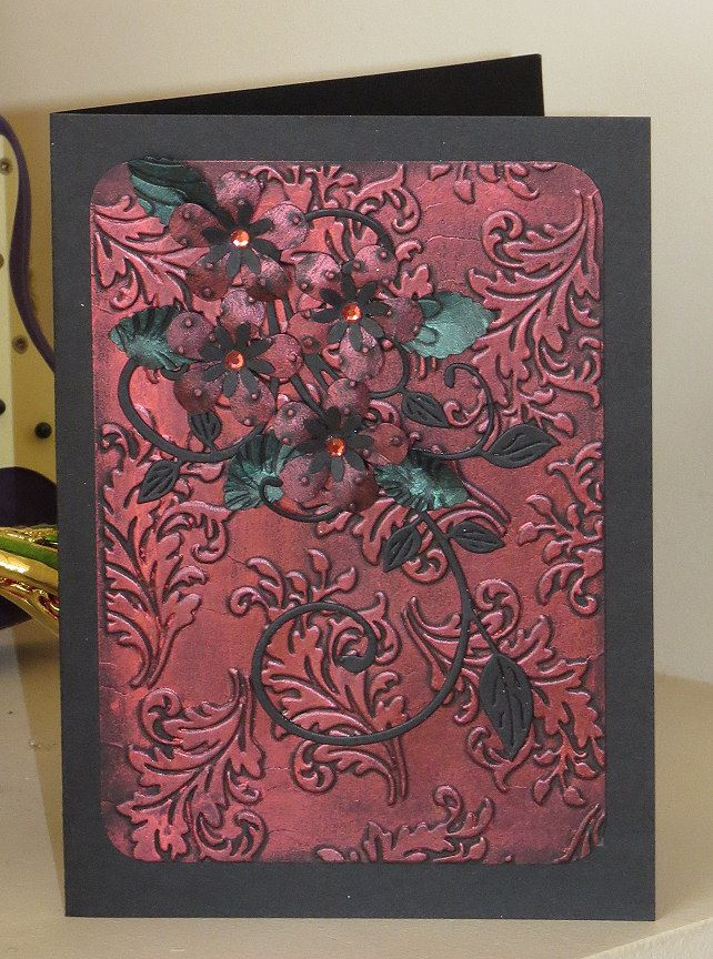 Red gilding wax on embossed leaf background.