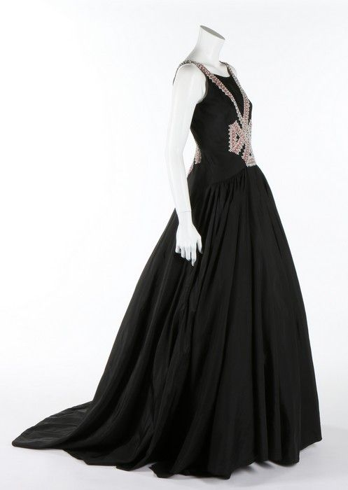 A Jeanne Lanvin couture sequined black taffeta evening gown, Summer, 1938. large woven label and pencil numbered 47997, the bodice with criss-crossed bands of pink and silver braid forming a knot to the front and embellished with large white beads held in place with tiny silver sequins
