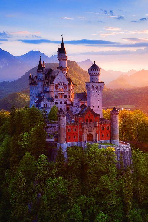 Neuschwanstein Castle on a rugged hill above the village ...