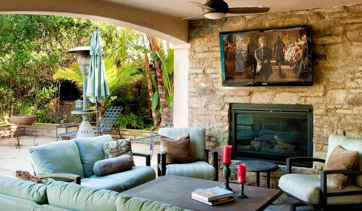 mediterranean backyard, covered patio, Los Angeles home, dark wood retractable glass doors, light green outdoor lounge furniture, glass coffee table, flat screen tv, stone fireplace, brown accent pillows, red candles, tropical landscaping