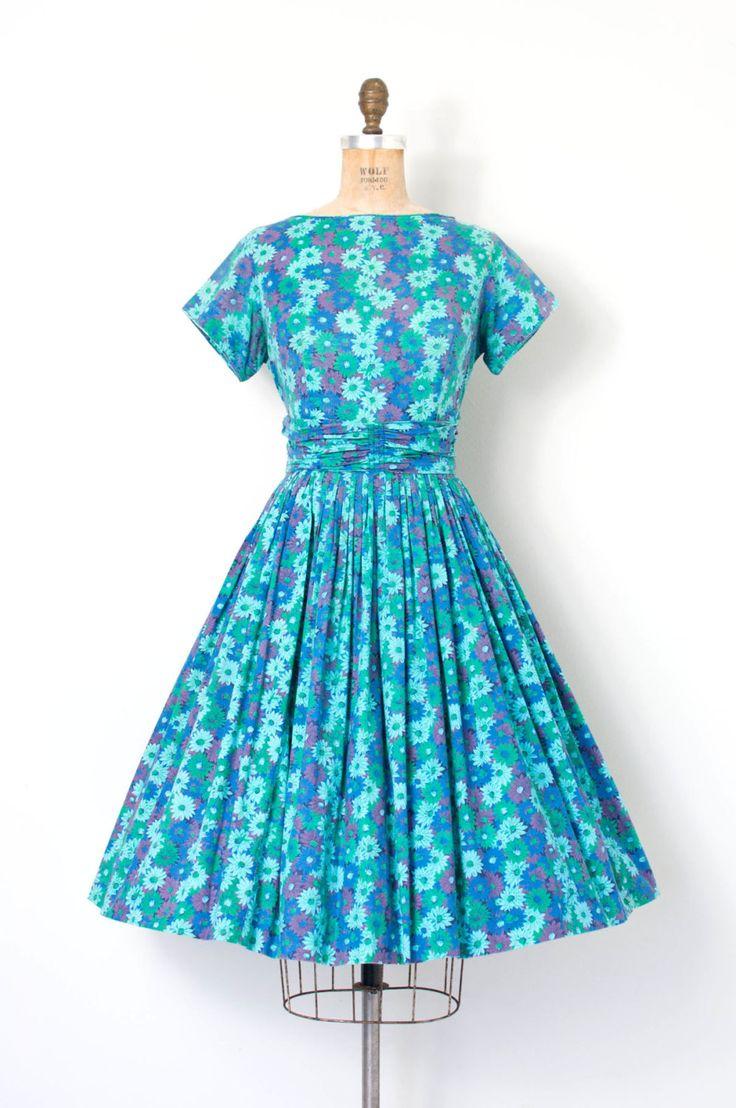 Vintage jaren 1950 kleden featuring een mooie bloemen print katoen in de blauwe, paarse en groene, korte mouwen, buste Darten, zelf bijgevoegde ruched cummerbund taille, volledige geplooide rok, metalen rits terug center bekroond met een haak en oog.  L EEN B E L Modus ODay | Vormgegeven in Californië  M E EEN S U R E M E N T S Bust 37 taille 29 heupen openen lengte 40.5  best past een medium.       |      |     |     |     |  zorg ervoor dat meten  |     |     |     |      C O N D I T IK O…