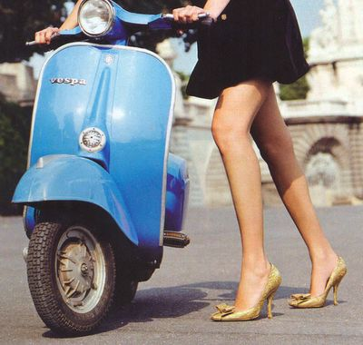 Riding a Vespa through some brick-laden European street. In a dress. And heels.