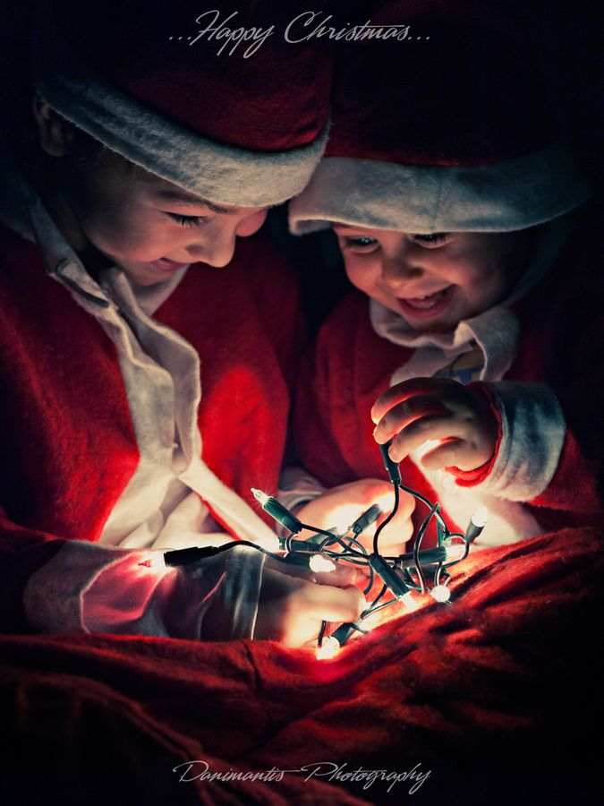 Colorful and contrasty photo of two smiling boys dressed like Santa holding warm white Christmas lights.