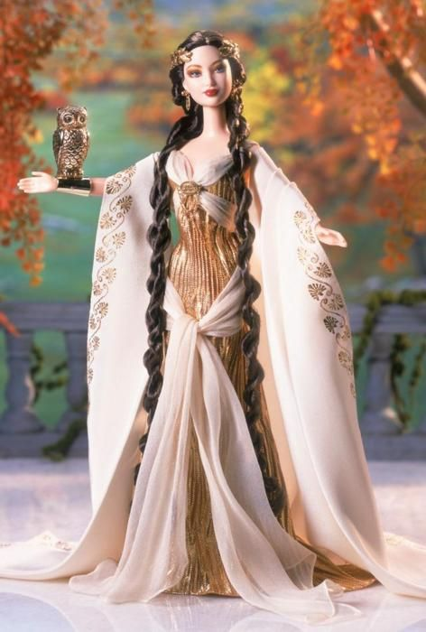Goddess of Wisdom Barbie wears an ivory palace crepe cape, embellished with golden Greek-inspired designs. The ensemble is completed with delicate sandals, golden earrings, and a headdress featuring a laurel leaf motif. Alighting on her antique gold-tone wrist cuff is her companion — an owl, the symbol of her great wisdom.