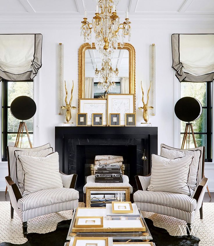 Gorgeous and glamorous space with black marble fireplace, gold accents. Ticking stripe relaxed roman shades. Interior design by Megan Winters