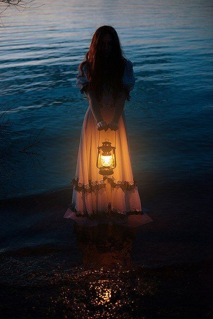woman holding a lantern standing in the lake at dusk...... photo
