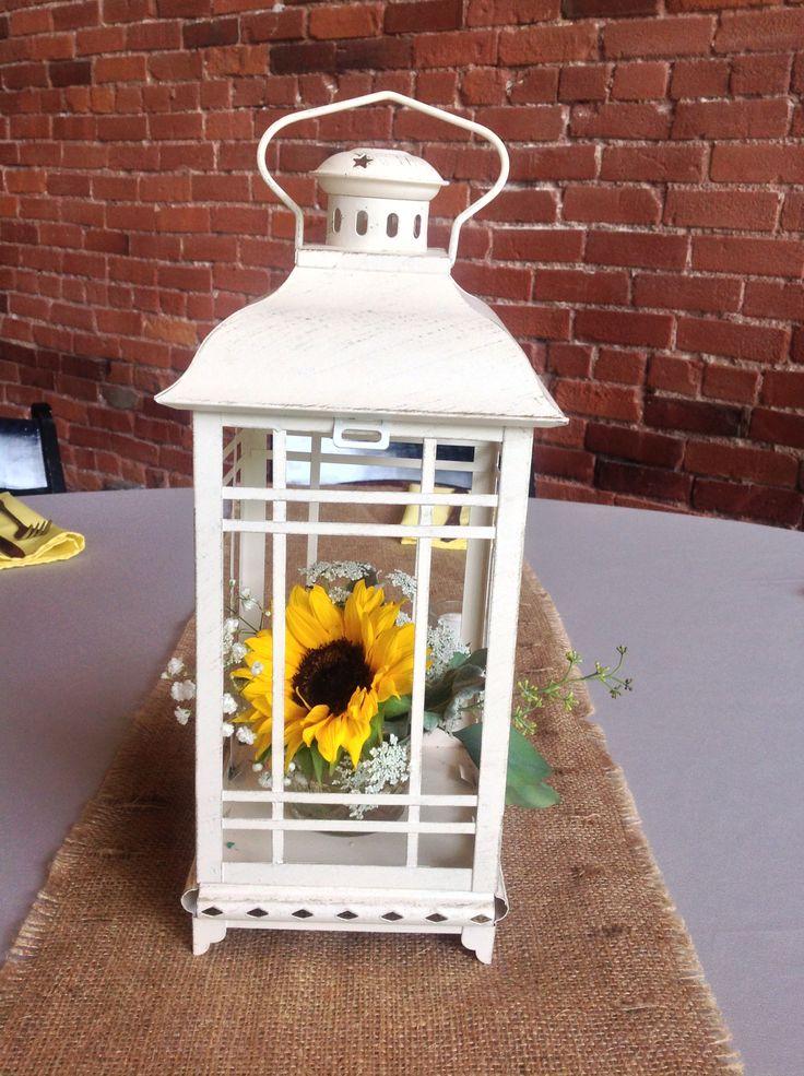 White lantern with a sunflower arrangement inside.