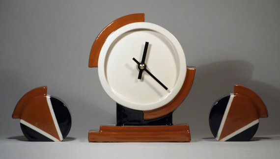This is a stylish and attractive ceramic mantel clock with matching left and right garnitures in an Art Deco inspired Aviator design. This clock has been hand glazed in our own Ivory white glaze with hand decorated black and brown glaze detail. The metal hour and minute hands finished in contrasting black. This glaze combination just screams out 1920s Jazz Age complementing the geometric design of this time piece very well.  The inspiration for our Aviator mantel clock comes from the rapid…