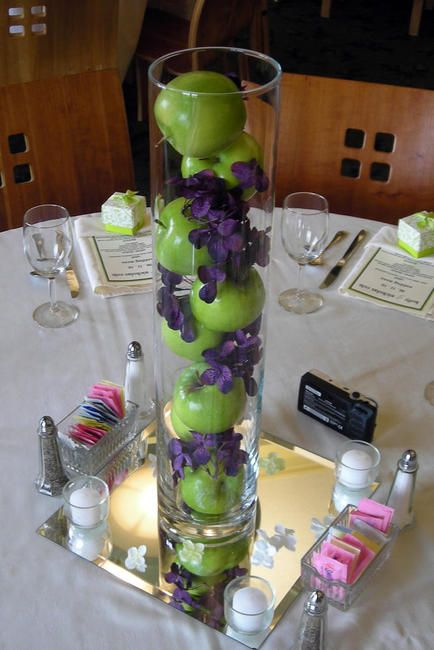 Stack green apples in a rented cylinder vase. Fill in the cracks with pieces of a silk hydrangea flower. Elite Events Rental | Nebraska