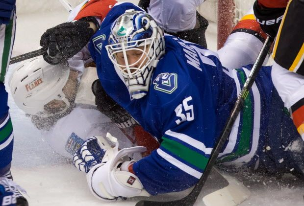 Vancouver Canucks goalie Jacob Markstrom, right is crashed into by Calgary Flames Kevin Westgarth, left during the first period of the final regular-season game at Rogers Arena in Vancouver, B.C. Sunday, April 13, 2014