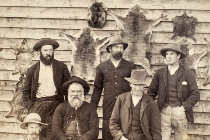 Original reason why koala sanctuaries were needed-  Bushmen and their dogs seated in front of a wall of animal skins (including koala pelts)