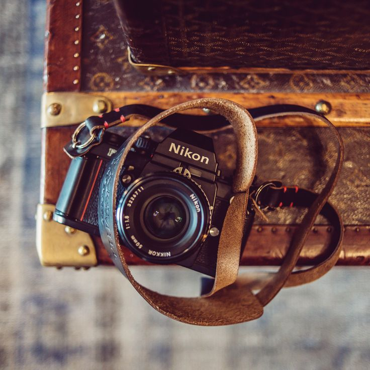 Louis Vuitton trunk with a Nikon F3 and our handmade black leather camera neck strap.