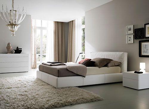 Lichtgrijze muur, zandkleurige vouwgordijnen, beige kleed, bruine/grijze dekbedovertrek