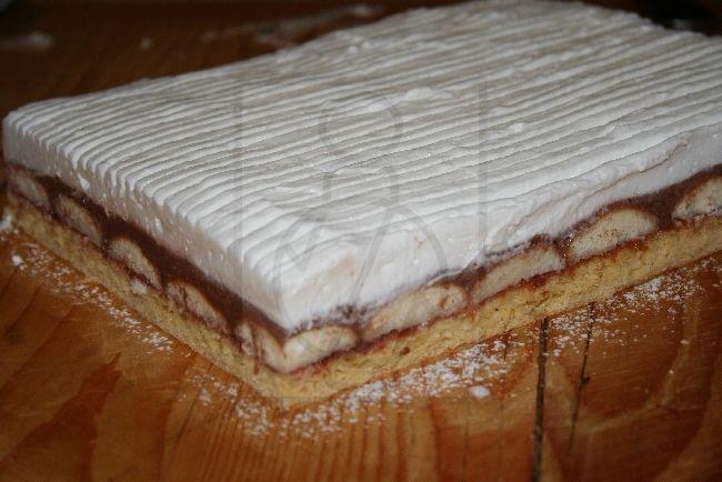 Sanftiger Kuchen,der aus dem Kokosteig, Kakaocreme und Biskuits besteht. Mit Sahne dekoriert.