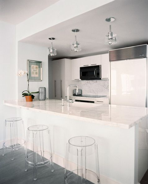 kuali cocinas - Modern Kitchen Cabinets - A modern kitchen with white marble and Lucite bar stools