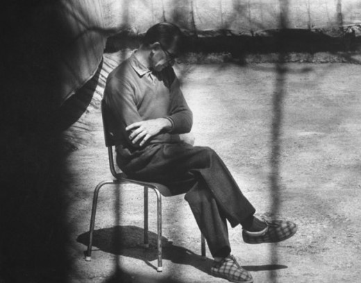 """Eichmann sits in courtyard during off times during his trial (April 11, 1961 at Beit-Ha'am Hebrew: """"House of the People"""" in Jerusalem.)  for crimes against humanity."""