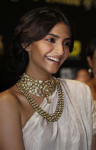 Sonam Kapoor poses on the green carpet at the 10th International Indian Film Awards. Love the kundan jewelry  and textured dress.
