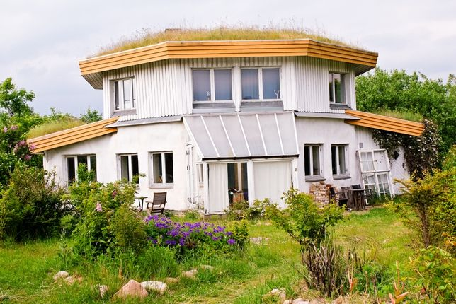 This octogonal house with a grass roof is part of a group of houses that the owners mostly built themselves. It's based on the idea that no square corners means it's easier to heat.    Serious attention is also paid to water -- the community uses 60-65% of the average Danish water consumption, thanks to compost toilets and rainwater collection for flush toilets, washing machines, and watering gardens.