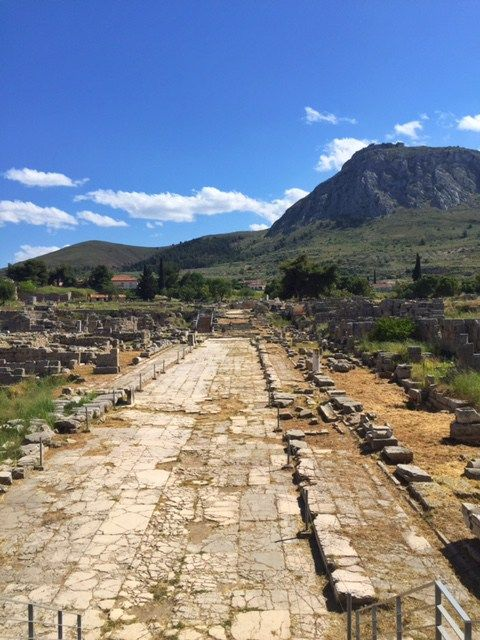 The stone paved Lechaion Road ancient Corinth with Acrocorinth in the distance
