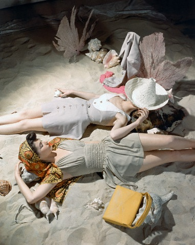 1941: Two models, one in a bolero and Celanese rayon bathing suit, the other in a print kerchief and Celanese rayon jersey suit, lying on sand surrounded by shells.