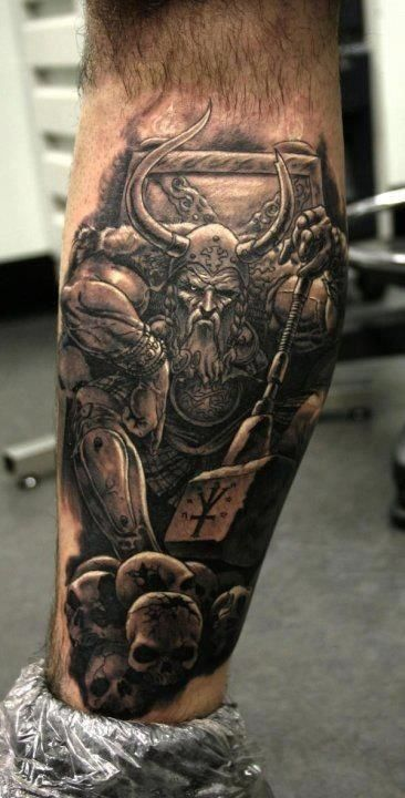Angry viking and skulls tattoo on leg