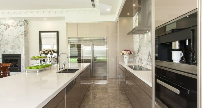 Sleek cabinetry in neutral tones allow the stone in this kitchen to do all the talking...