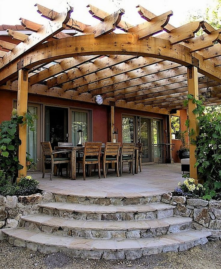 This nice backyard pergola is cool and shady. The frame and shape of the roof is curved which gives it an interesting element, breaking the monotony. The roof is not fully covered. The planks settled in horizontal and vertical directions allow the sunlight to peek in from the small squares. The stone deck is giving the pergola a strong character.