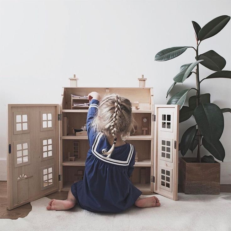 Cute little girl in sailor dress playing with dolls house