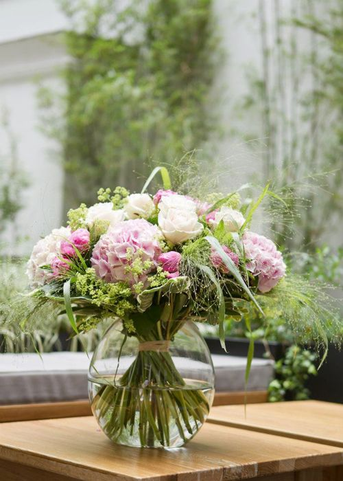 a hand-tied bouquet using peonies, roses, hydrangeas, alchemilla mollis, hosta leaves, pittosporum and fountain grass.