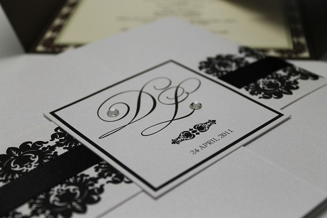 Bold black and white invite - a wrap with a monogram square and Swarovski crystal elements and black printed details closes the invitation.    www.facebook.com/RubyGreyCreative