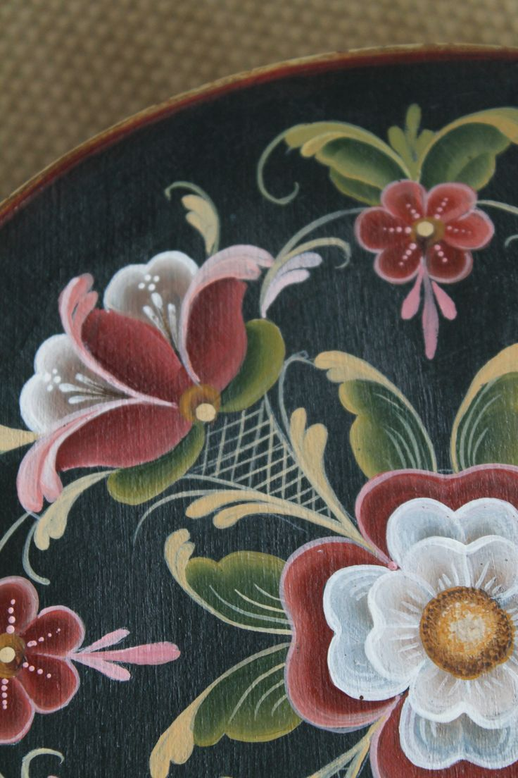 Detailing of rosemaling on a round wooden box. Distinctive colours common to the style.