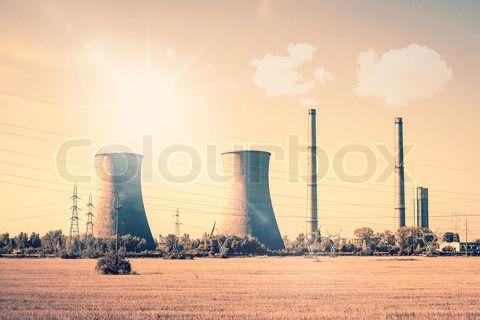 Stock image of 'Smoking powerplant chimneys in the sun'
