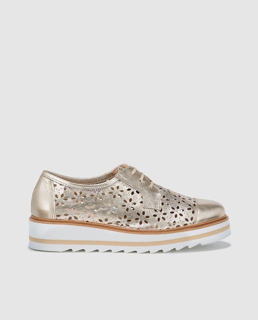 Zapatos de cordones de piel troquelada en color oro, cierre de cordones y cuña media.