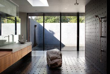 A large rock is placed in the center of the master shower as a seat  A mirror and glass wall are suspended in front of the pre-cast concrete wall in order to provide reflections of the exterior water feature and courtyard   Photography by Andrew Fabin #bathroomdesign