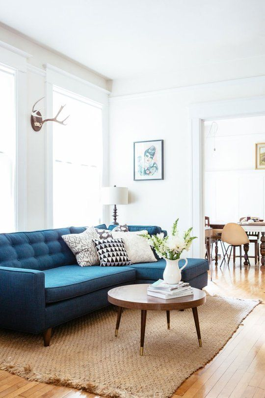 White and bright room. Pretty mid-century modern inspired blue tufted sofa with round coffee table.