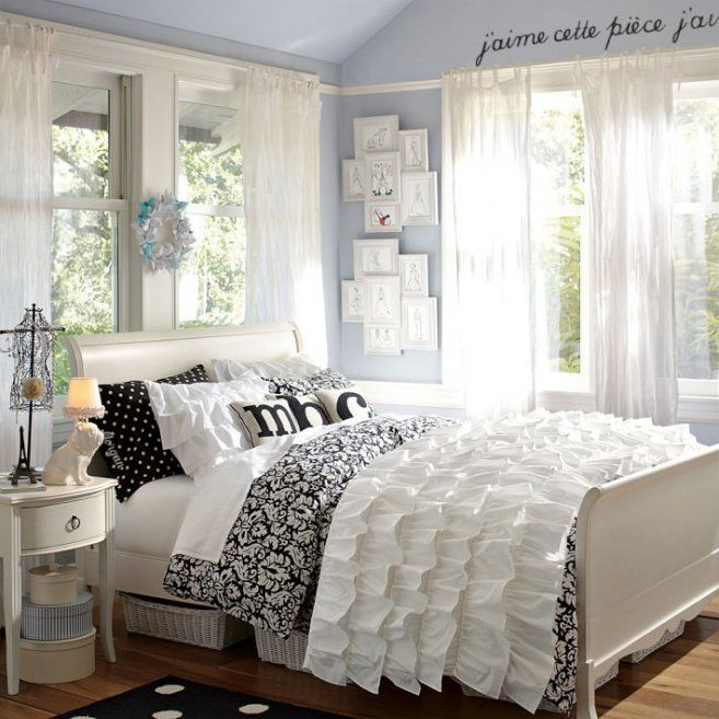 Pale blue/grey walls, white furniture, black accents.