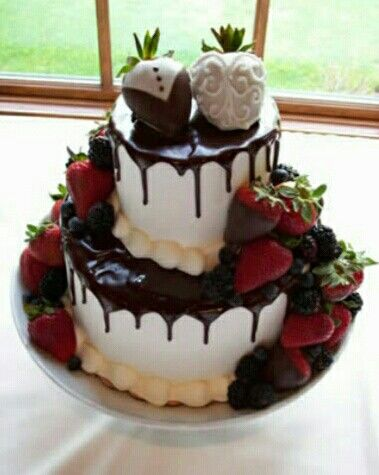 Chocolate dripped white wedding cake with strawberry bride and groom