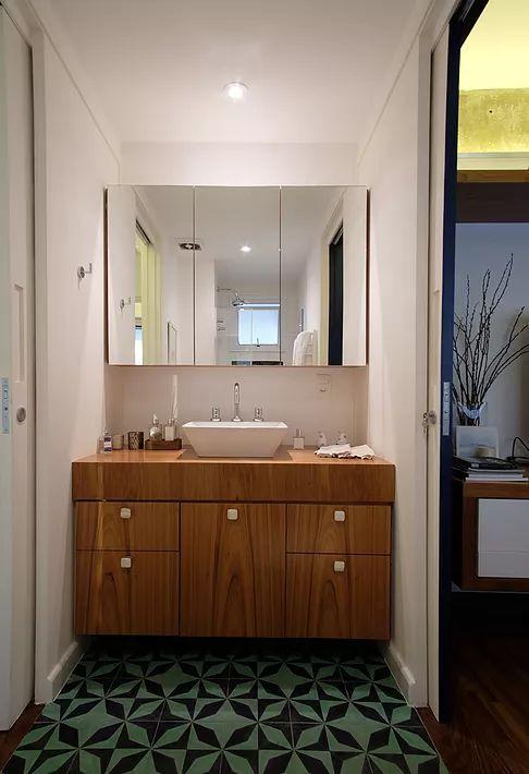 Banheiro com piso em ladrilho hidráulico. Cuba de apoio. Armário com espelho. Bancada de madeira.