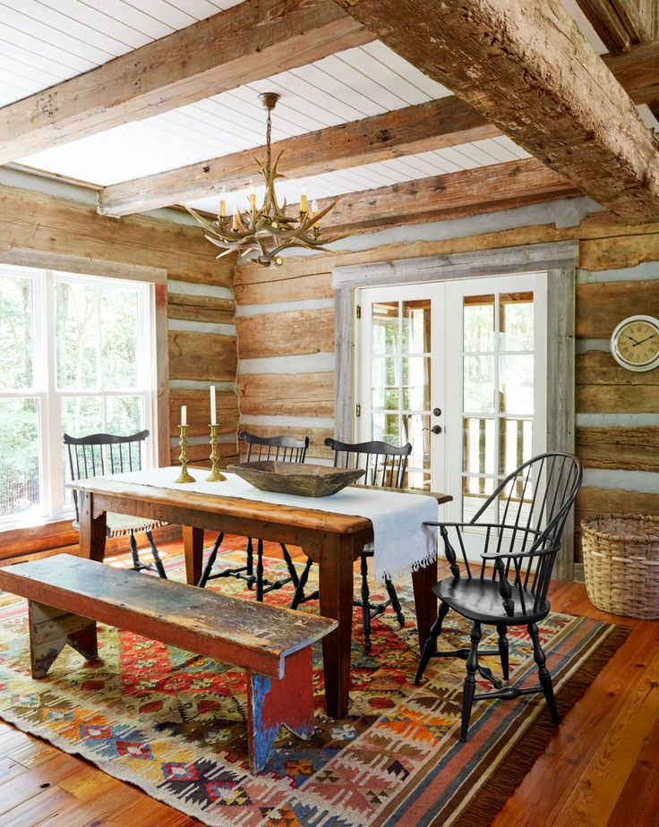 """Dining Room :  A mix of black Windsors hand-crafted by Lawrence Crouse Workshop surrounds the farm table. The painted bench is a throwback to Jimmy's childhood """"when there was always a bench for the kids to sit on,"""" he says. In between the beams, Julie painted the paneled ceiling—made of new wood—Snow White by Benjamin Moore, a look she continued throughout the house"""