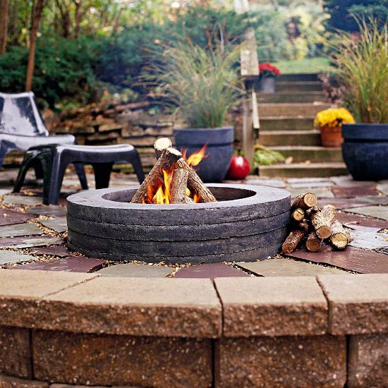 """Better Homes & Gardens: """"The homeowner built his own fire pit with concrete culvert spacers -- aka doughnuts -- intended to fill culvert gaps in city sewer systems. Using 2-inch thick spacers, he nestled the first one halfway into pea gravel, then stacked the rest on top. He finished by painting the spacers with a concrete stain to darken and soften their utilitarian look."""""""