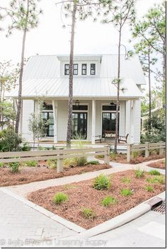 Watercolor House Tour- love the white siding with dark bronze windows and a tin roof